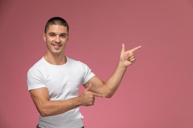 Jovem homem de camisa branca, de frente para a frente, posando com uma expressão apontando no fundo rosa Foto gratuita