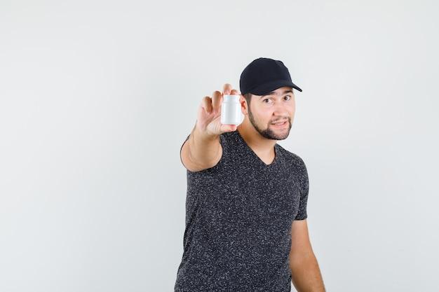 Jovem homem de camiseta e boné segurando um frasco plástico de comprimidos Foto gratuita