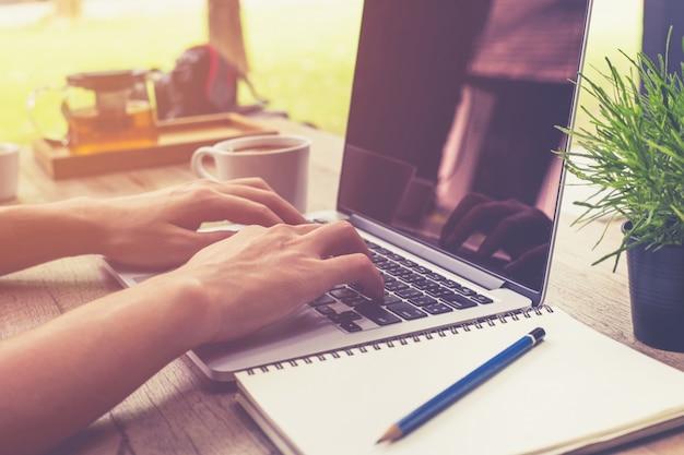 Jovem homem de negócios mão segurando copo café e usando computador portátil na cafeteria com vintage tonificado. Foto Premium