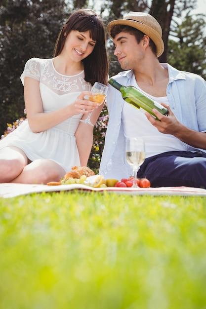 Jovem homem derrama a mulher vinho em um copo durante um piquenique Foto Premium