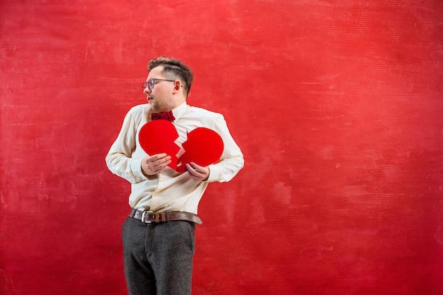 Jovem homem engraçado com coração partido abstrata Foto gratuita