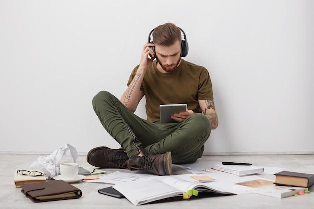 Jovem homem estiloso ouve música com fones de ouvido, segura um tablet moderno e se comunica com amigos ou parentes online Foto gratuita