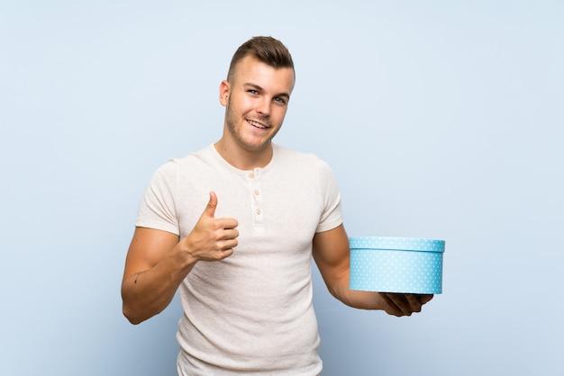 Jovem homem loiro bonito sobre parede azul isolada, segurando a caixa de presente Foto Premium