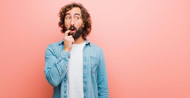 Jovem homem louco barbudo com olhar surpreso, nervoso, preocupado ou assustado, olhando para o lado em direção ao espaço da cópia contra a parede de cor lisa Foto Premium