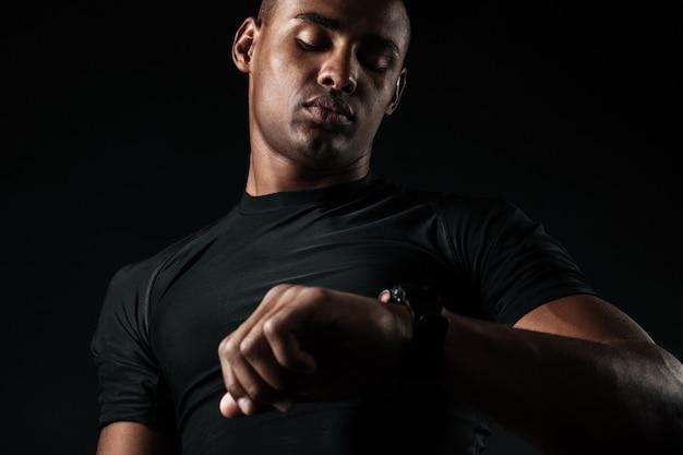Jovem homem musculoso africano, olhando para o relógio Foto gratuita
