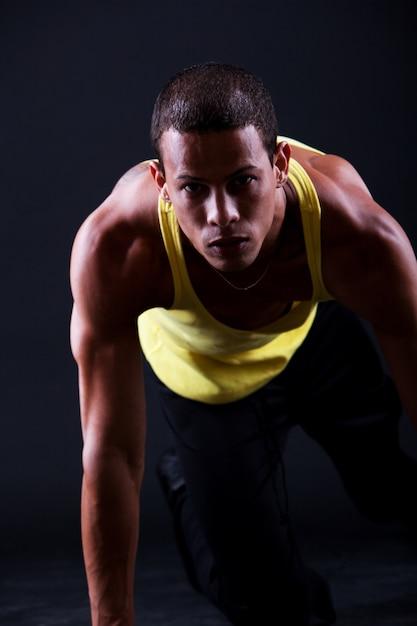 Jovem homem musculoso está pronto para correr Foto gratuita