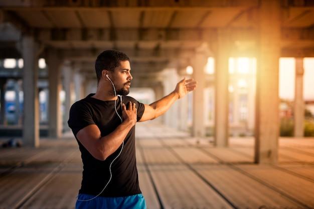 Jovem homem musculoso se alongando e se preparando para um treinamento físico Foto gratuita