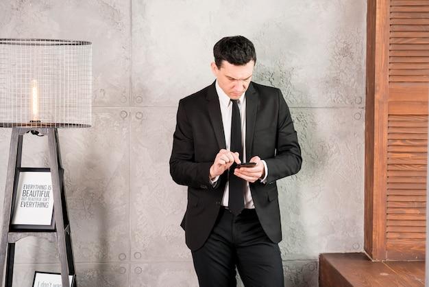 Jovem, homem negócios, com, smartphone, ficar, por, parede Foto gratuita