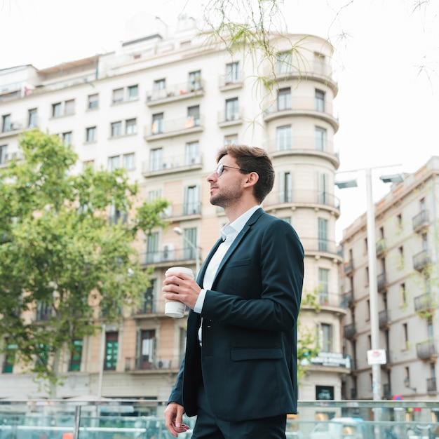 Jovem, homem negócios fica, frente, predios, xícara café segurando, em, mão Foto gratuita
