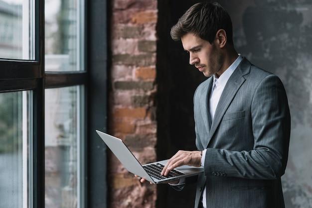 Jovem, homem negócios fica, perto, a, janela, usando computador portátil Foto gratuita