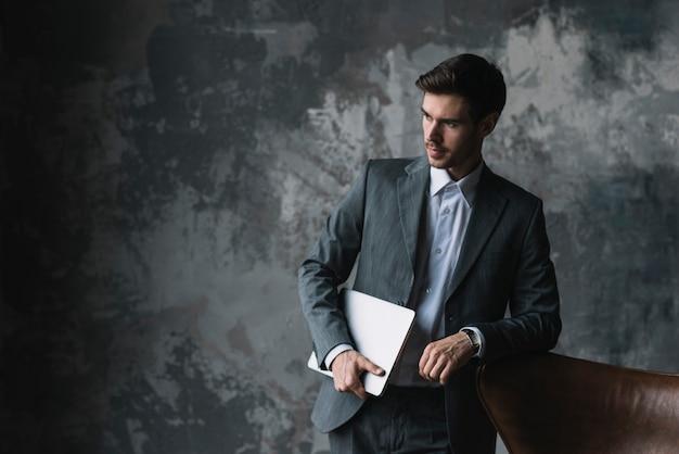 Jovem, homem negócios, inclinar-se, cadeira, segurando, laptop, em, seu, mão, contra, grunge, fundo Foto gratuita
