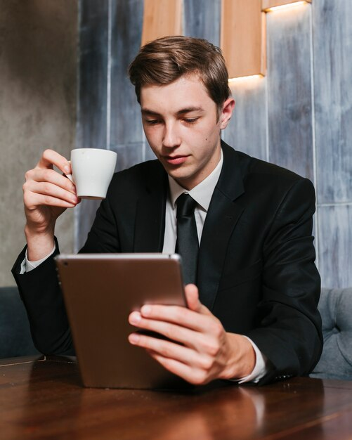 Jovem, homem negócios, olhar, a, tabuleta Foto gratuita