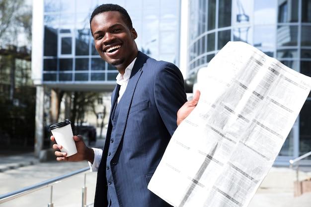 Jovem, homem negócios, segurando, descartável, xícara café, mostrando, jornal, direção, câmera Foto gratuita