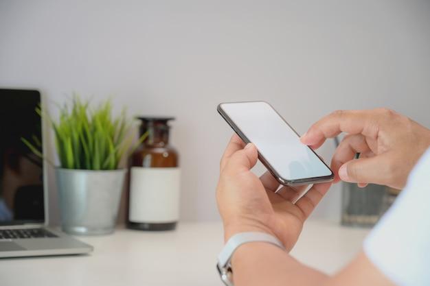 Jovem, homem negócios, segurando, smartphone, em, um, espaço de trabalho Foto Premium