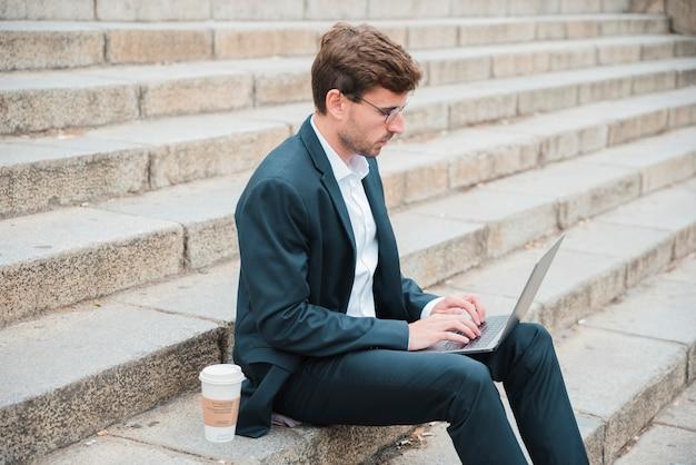 Jovem, homem negócios, sentando, ligado, escadaria, com, descartável, xícara café, usando computador portátil Foto gratuita