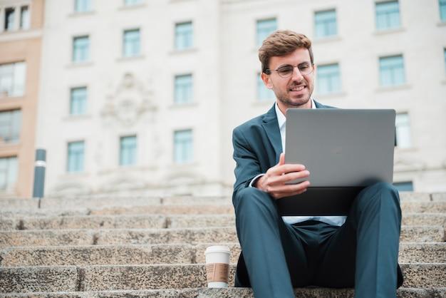 Jovem, homem negócios, sentando, ligado, escadaria, de, edifícios, usando computador portátil Foto gratuita