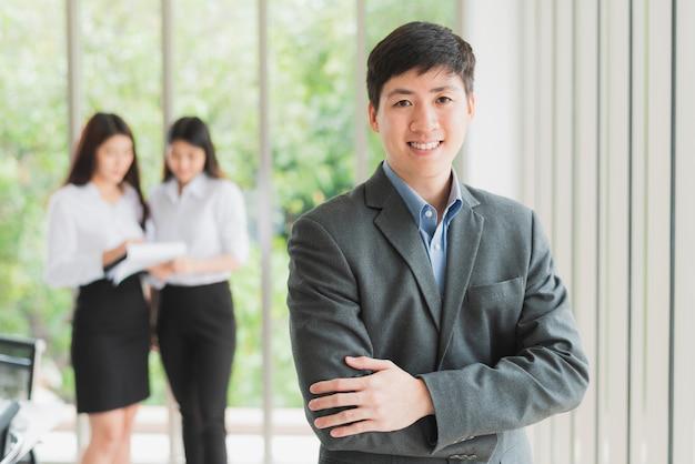 Jovem, homem negócios, sorrindo, com, braços cruzaram Foto Premium