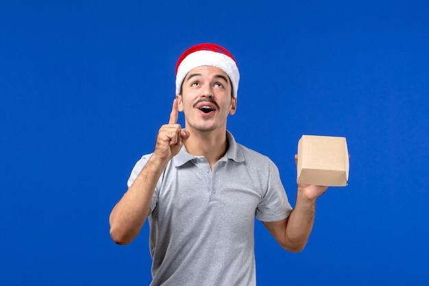 Jovem homem segurando um pacote de comida na parede azul de serviço masculino de comida de frente Foto gratuita