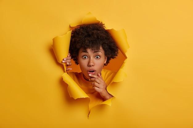 Jovem imaginou uma jovem com penteado afro, abre a boca, fica em pé no fundo do buraco de papel rasgado Foto gratuita