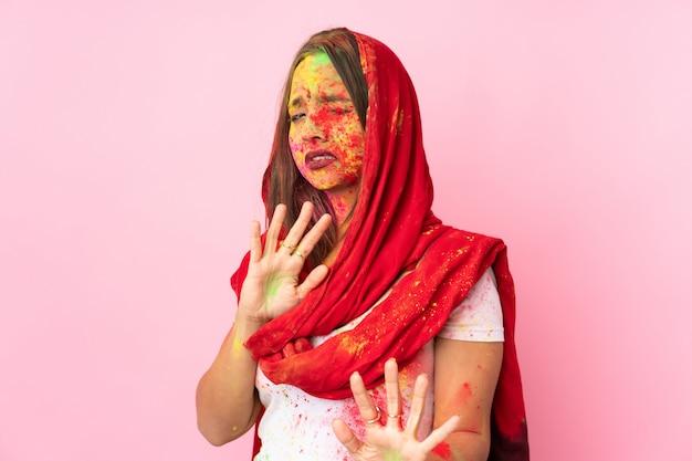 Jovem indiana com pós coloridos de holi no rosto na parede rosa nervosa esticando as mãos para a frente Foto Premium
