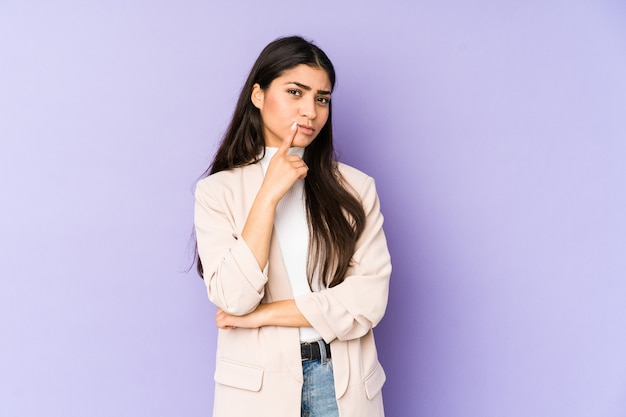Jovem indiana isolada em um fundo roxo, olhando de soslaio com expressão duvidosa e cética. Foto Premium