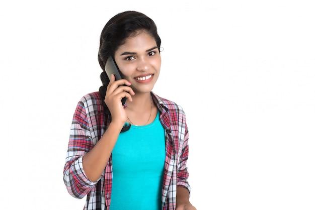 Jovem indiana usando um telefone celular ou smartphone isolado em uma parede branca Foto Premium