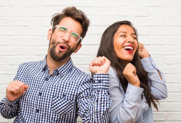 Jovem, indianas, mulher, e, caucasiano, par homem, escutar música, dançar, e, tendo divertimento, em movimento, shouting, e, expressar, felicidade, liberdade, conceito Foto Premium
