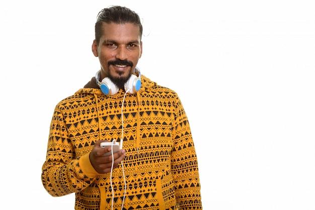 Jovem indiano feliz sorrindo, segurando um telefone celular e usando fones de ouvido no pescoço isolado Foto Premium