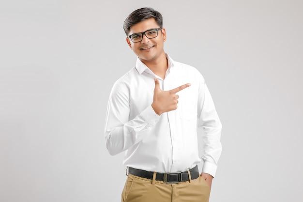 Jovem indiano mostrando a direção com a mão Foto Premium