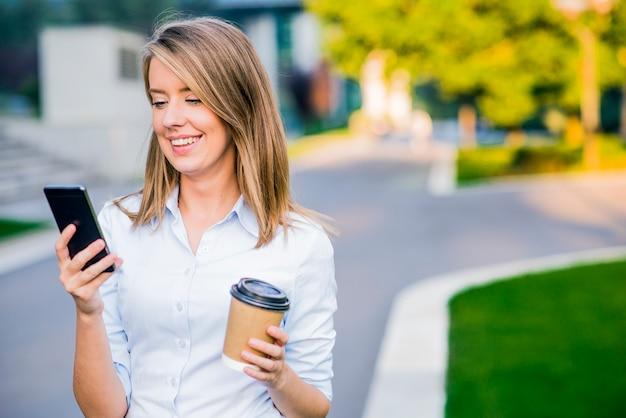 Jovem inteligente mulher profissional lendo usando o telefone. empresária feminina lendo notícias ou sms sms no smartphone enquanto toma café na quebra do trabalho. Foto gratuita