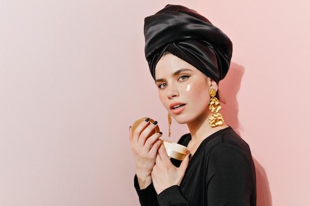 Jovem interessada em joias fazendo sua rotina de cuidados com a pele Foto gratuita