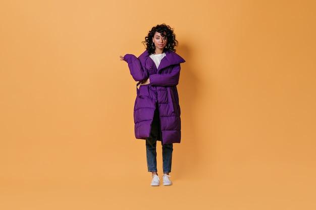 Jovem interessada posando com uma jaqueta roxa Foto gratuita