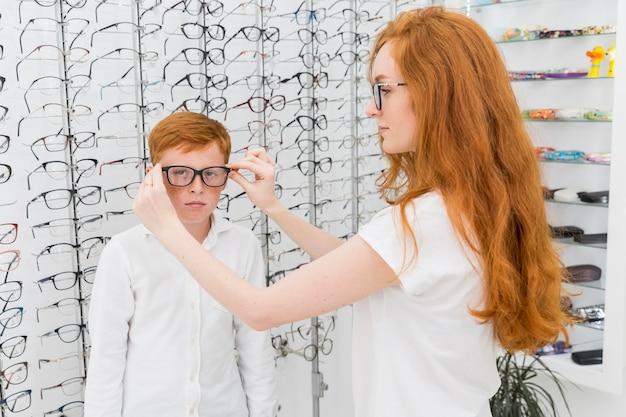 Jovem irmã usando óculos para o irmão na loja de óptica Foto gratuita