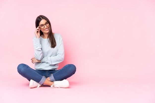 Jovem isolada na parede rosa com óculos e feliz Foto Premium