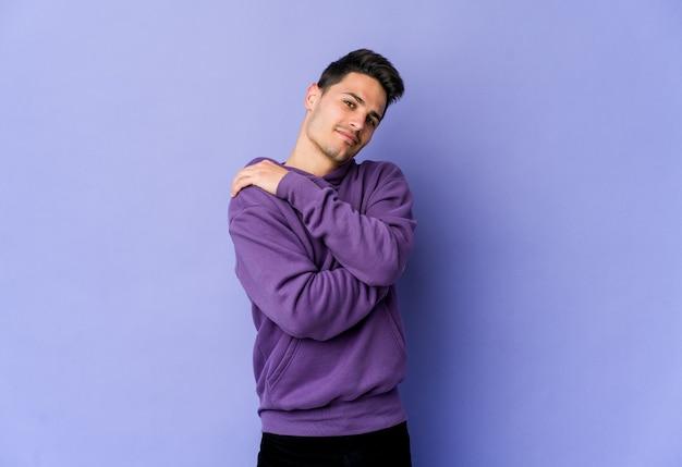 Jovem isolado na parede roxa se abraçando, sorrindo despreocupado e feliz Foto Premium