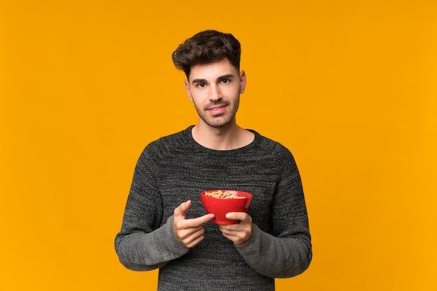 Jovem isolado segurando uma tigela de cereais Foto Premium