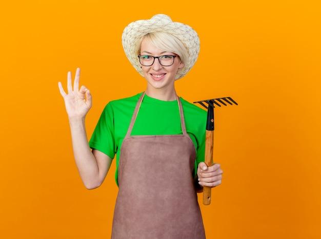 Jovem jardineira com cabelo curto no avental e chapéu segurando um mini ancinho olhando para a câmera sorrindo mostrando uma placa de ok em pé sobre um fundo laranja Foto gratuita