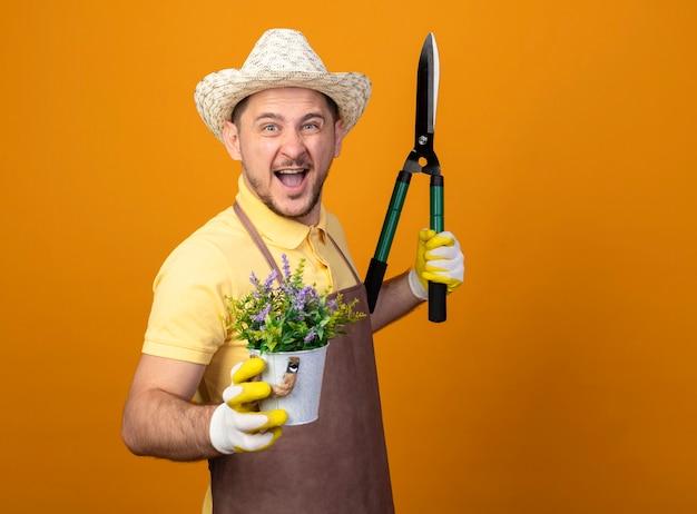 Jovem jardineiro alegre vestindo macacão e chapéu segurando uma tesoura de sebes e um vaso de plantas sorrindo, feliz e animado Foto gratuita