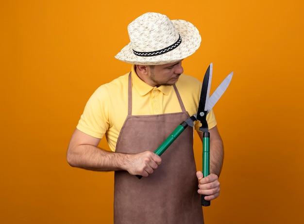 Jovem jardineiro de macacão e chapéu segurando um cortador de cerca viva, olhando para ele intrigado em pé sobre uma parede laranja Foto gratuita