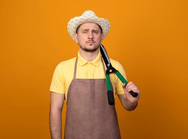 Jovem jardineiro de macacão e chapéu segurando uma tesoura de sebes no ombro com uma expressão séria e confiante Foto gratuita