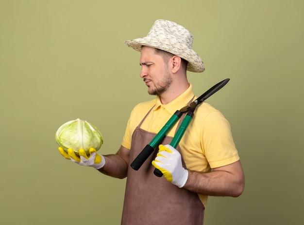 Jovem jardineiro vestindo macacão e chapéu em luvas de trabalho segurando um cortador de cerca viva e repolho olhando para ele com uma cara séria Foto gratuita