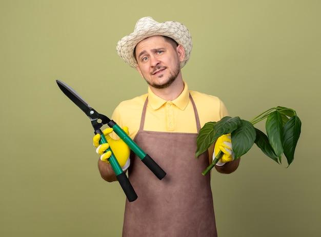 Jovem jardineiro vestindo macacão e chapéu em luvas de trabalho segurando um cortador de plantas e sebes sorrindo com uma cara feliz Foto gratuita