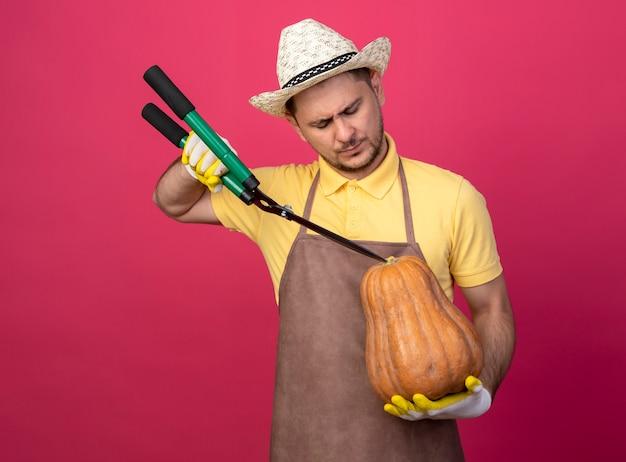 Jovem jardineiro vestindo macacão e chapéu em luvas de trabalho segurando uma abóbora e vai cortá-la usando um corta-sebes em pé sobre a parede rosa Foto gratuita