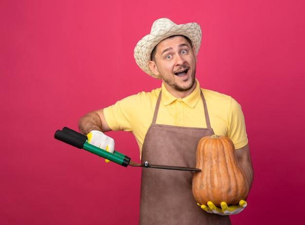 Jovem jardineiro vestindo macacão e chapéu em luvas de trabalho segurando uma abóbora e vai cortá-la usando um corta-sebes feliz e positivo em pé sobre a parede rosa Foto gratuita