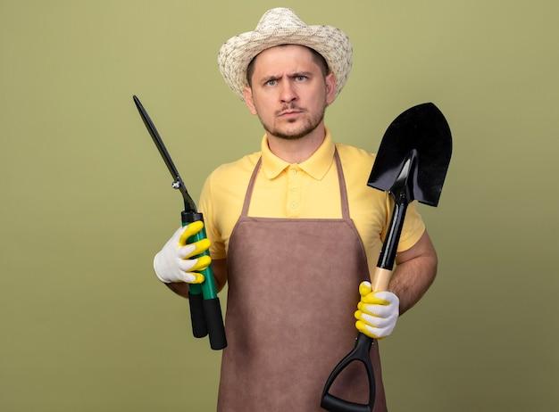 Jovem jardineiro vestindo macacão e chapéu em luvas de trabalho segurando uma pá e um cortador de cerca viva com uma expressão séria Foto gratuita