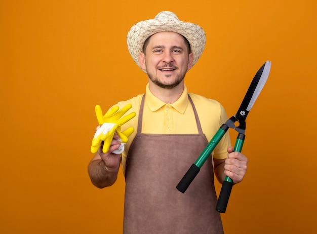 Jovem jardineiro vestindo macacão e chapéu segurando luvas de trabalho e corta-sebes com um sorriso no rosto Foto gratuita