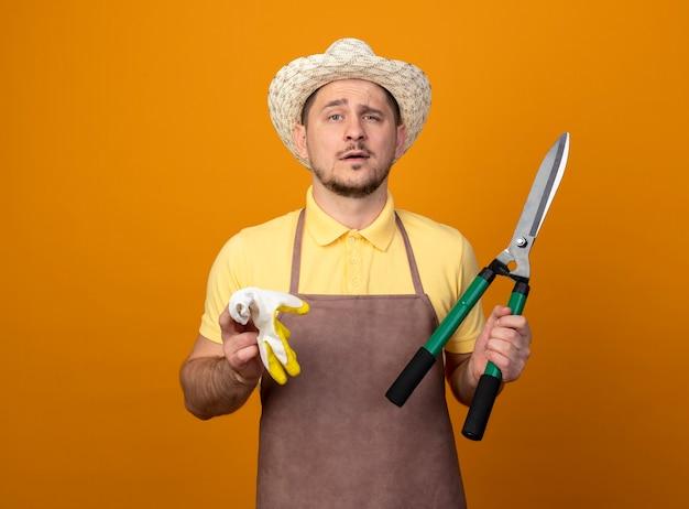 Jovem jardineiro vestindo macacão e chapéu segurando luvas de trabalho e corta-sebes olhando para frente com expressão confiante em pé sobre a parede laranja Foto gratuita