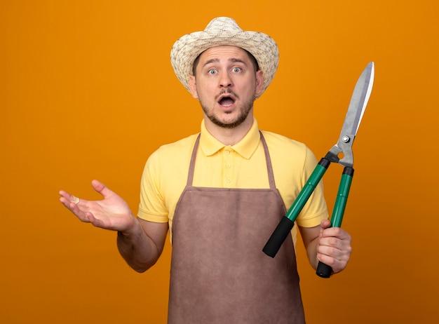 Jovem jardineiro vestindo macacão e chapéu segurando um cortador de cerca viva olhando para a frente espantado e surpreso em pé sobre a parede laranja Foto gratuita