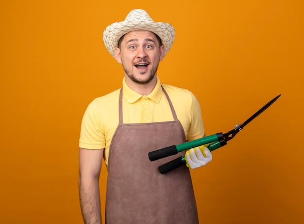 Jovem jardineiro vestindo macacão e chapéu segurando um cortador de cerca viva olhando para a frente feliz e surpreso em pé sobre a parede laranja Foto gratuita
