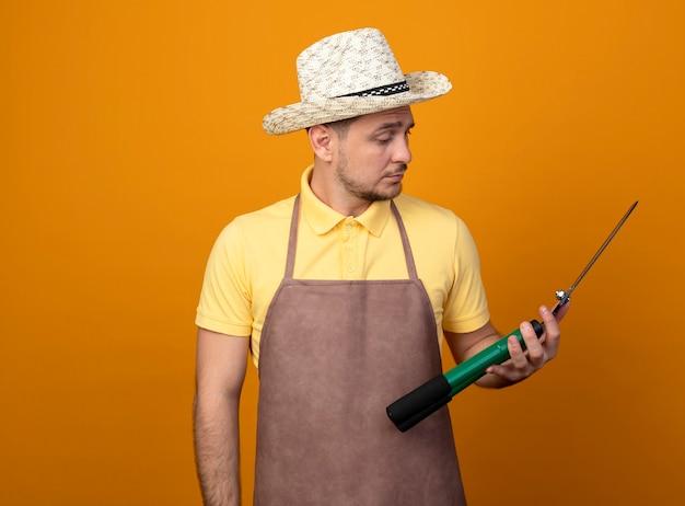Jovem jardineiro vestindo macacão e chapéu segurando um cortador de cerca viva olhando para ela com uma cara séria em pé sobre a parede laranja Foto gratuita